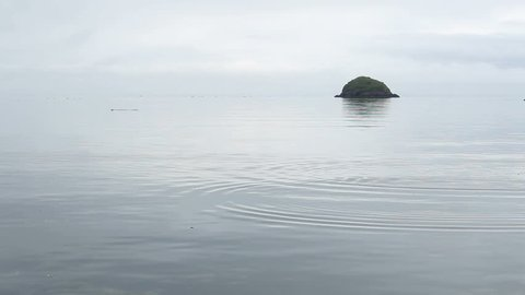 Flat, smooth stone tossed into water ripples across surface towards green, jutting boulder off coast of Kodiak Island, Alaska. 1080p