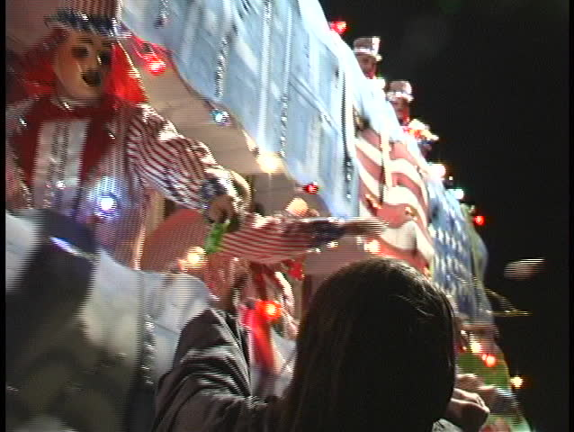 NEW ORLEANS, LA - CIRCA 2006: A woman catches several souvenirs given out by a passing float during the Mardi Gras parade circa 2006 in New Orleans, LA. | Shutterstock HD Video #1440916