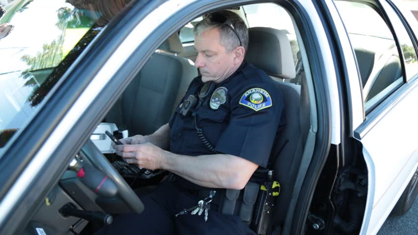 Anaheim, CA., January 2016: Police Officer checking his cell phone in a patrol car in Anaheim, CA., January 2016.