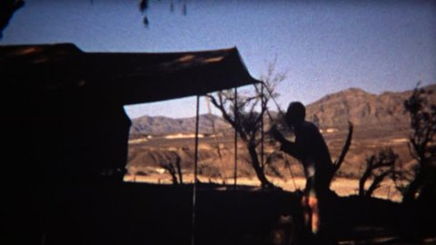 DEATH VALLEY, CA. 1972: Man setting up camping tent silhouette with beautiful mountain background.