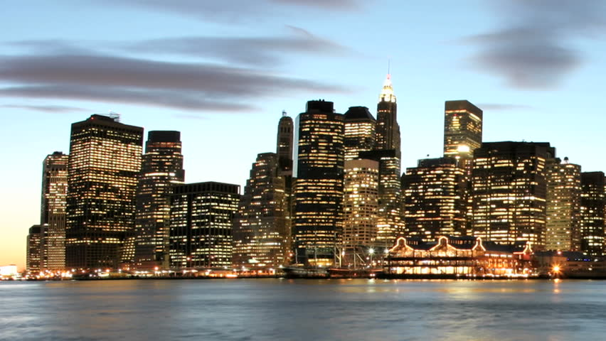 Slow pan of a time-lapsed shot of clouds in shades of pink and purple passing over the New York City skyline as golden-hour changes to night. | Shutterstock HD Video #1444963