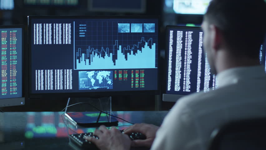 Man is working on a computer with data and graphs in a dark office filled with display screens. Shot on RED Cinema Camera in 4K (UHD).