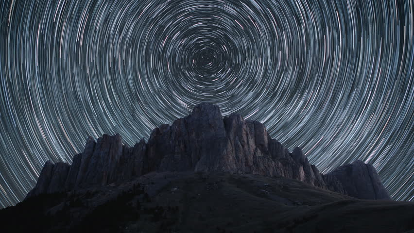 Beautiful star trails time-lapse over the rocky mountains. Polar North Star at the center of rotation. 4K resolution.