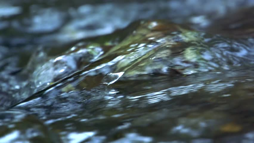 Slowmotion detail of water flows across the stone