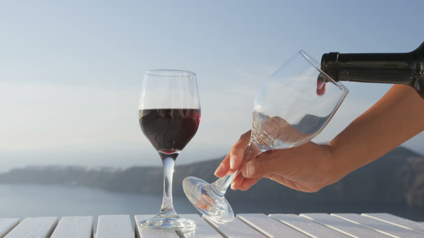 Waiter serving red wine pouring wine in to glass from red wine bottle. Hands of female pouring red wine in glass on table. Woman is serving alcohol in naturet during vacation on Santorini, Greece.