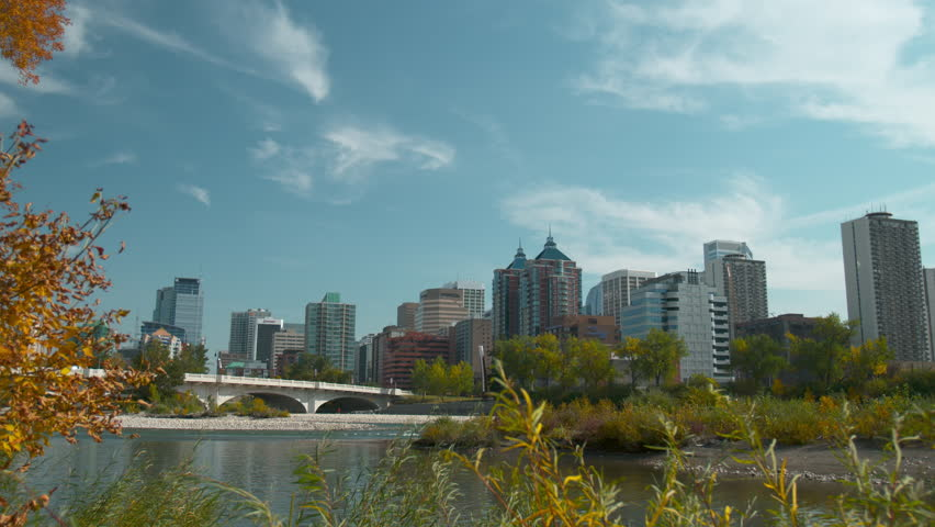 Shot of the Calgary skyline/downtown from across the Bow river with the river in the foreground.  Has the Louise Riley bridge in the foreground as well.  Shot in early autumn.