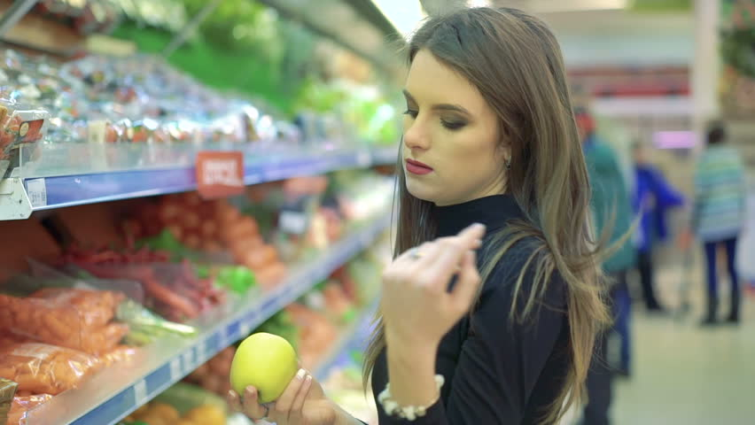 Beautiful young woman shopping for fruits products at a grocery market. | Shutterstock HD Video #14644645