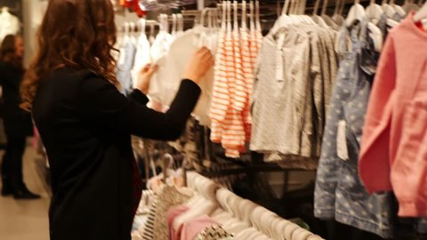 millennial pregnant woman choosing Baby Clothing in baby and maternity shop