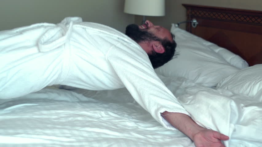 Young, happy man falling on bed, super slow motion 240fps