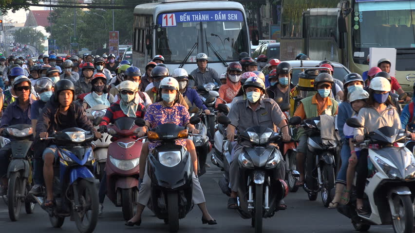 SAIGON, VIETNAM - 4 DECEMBER 2015: Heavy rush hour traffic, motorbike riders on the busy roads in downtown Saigon (HCMC) in urban Vietnam