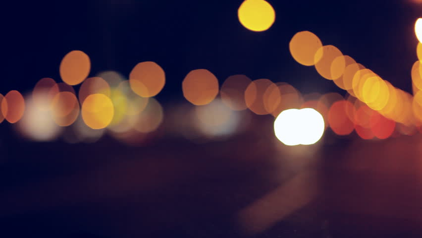 Driving at night. Windshield view and blurred cars in city. Illuminated front car window with blurred city traffic on town streets. #14708773