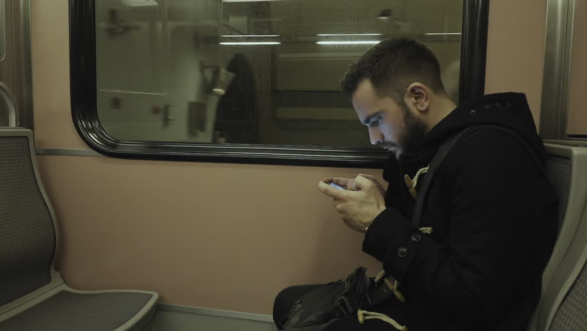 Young man traveling by train/subway playing and passing time on tablet.HD clip of a young man using his tablet while commuting on the metro train.Train arriving to the destination/station. | Shutterstock HD Video #14709853