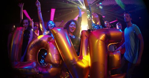 Young attractive multi-ethnic friends holding inflatable golden balloons spelling love during party in a trendy confetti filled nightclub dance floor.