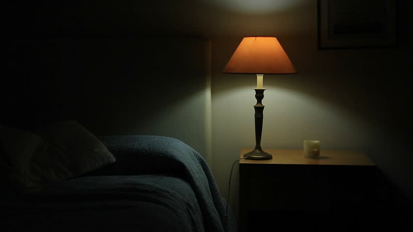 Man prepares to go to bed and sleep. Person lays down in bed and turns off night stand besides bed