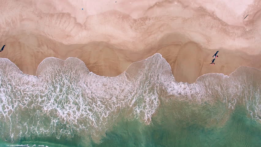 Aerial View Of Ocean Waves Crashing On Beach With People Walking By 4K Drone Footage