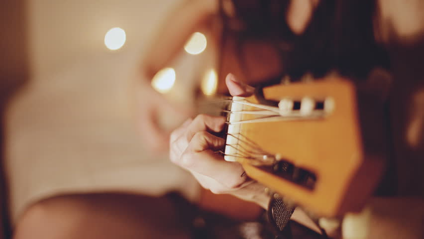 the young girl plays an acoustic guitar