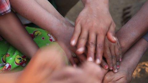 Many connecting children's hands. Mrauk-U, Myanmar