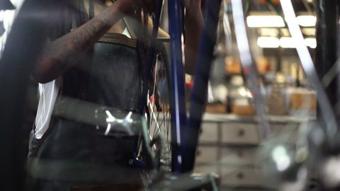 Afro-american woman with dreads and tattoos fixing a bicycle wheel in her repair workshop where she works as a skilled bike mechanic