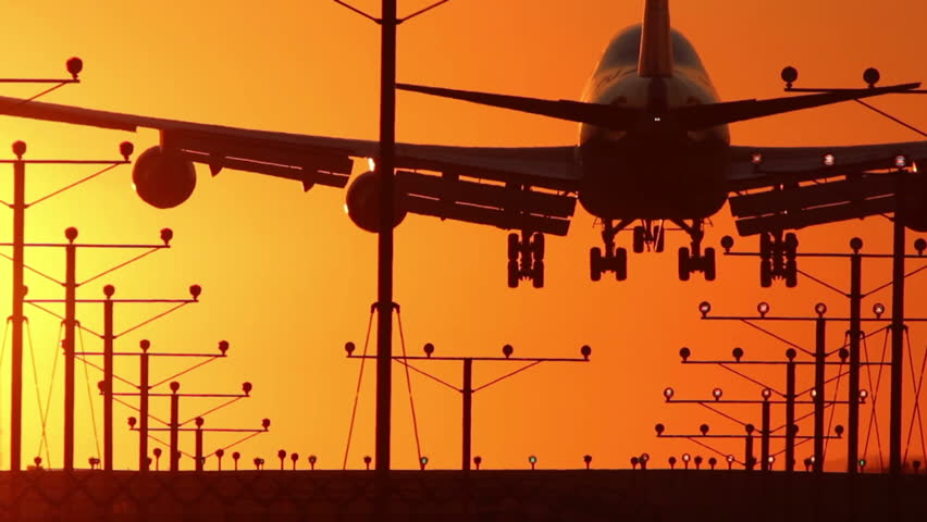 HD footage of a 4 engine jumbo jet plane landing in silhouette against an orange sunset sky, followed by a defocus / camera blur out.  Jet engine audio included. | Shutterstock HD Video #1475731