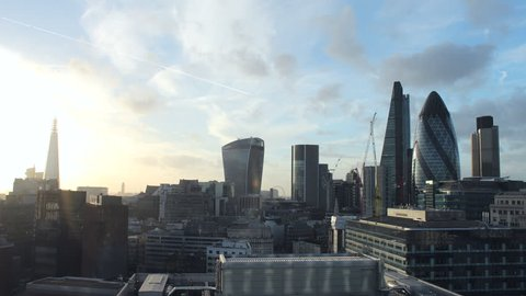 Time lapse video of the City of London financial district on a sunny day. The Shard, Walk-ie Talkie, Cheese Grater, and Gherkin buildings. Sun and clouds with aircraft contrails.