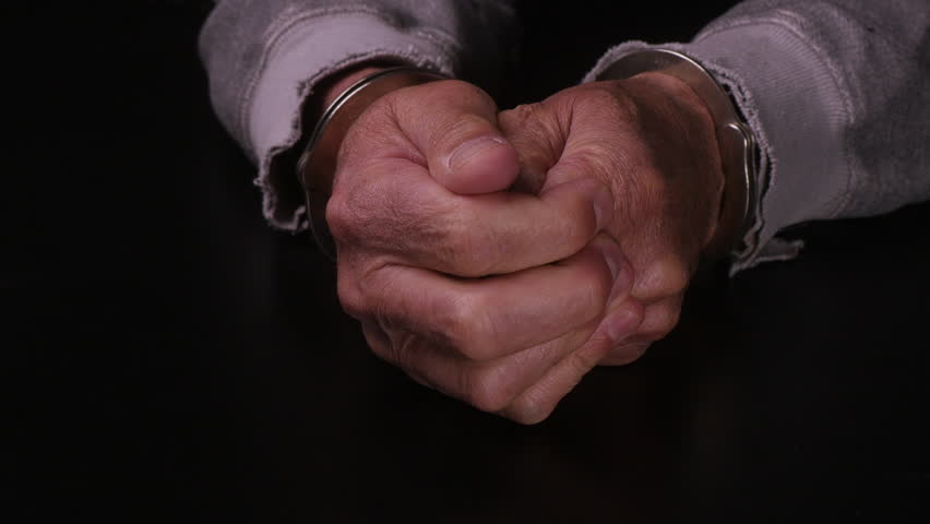 MALE HANDS IN HANDCUFFS.  PAIR OF HANDS TESTS OUT THE STRENGTH OF THE CUFFS.  CLOSE UP SHOT, ARMS IN TATTERED SWEATSHIRT ON A BLACK TABLETOP.  SHOT IN 4K.  AUDIO. | Shutterstock HD Video #14769583