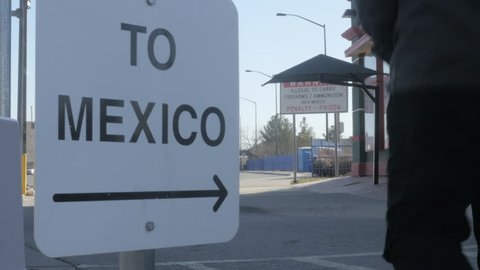4K shot of camera following a man in a hat and jacket who is walking toward the border crossing from US to Mexico on a sunny day.