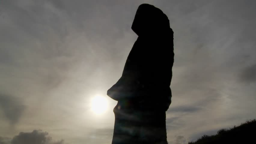 Clouds move behind Easter Island statues.
