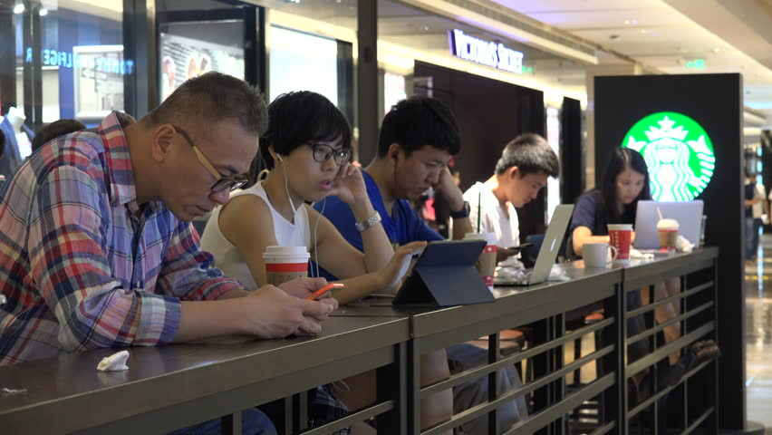 SHENZHEN, CHINA - 22 NOVEMBER 2015: Chinese business people use their smartphones and laptops, while at work in a Starbucks coffee shop in Shenzhen