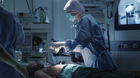 Medical Team Performing Defibrillation in Modern Operating Room. Shot on RED Cinema Camera.
