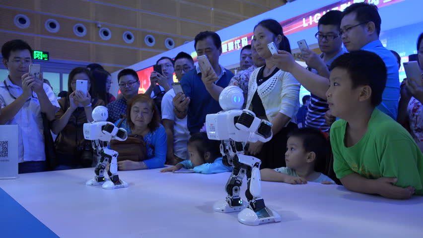 SHENZHEN, CHINA - 20 NOVEMBER 2015: Dancing robots, Gangnam Style (audio stripped), children and their parents, technology trade show, future generation, Shenzhen, China