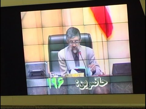 Parliament, Tehran, Iran - 2005 - Chairman of the Iranian Parliament, Gholam Ali Haddad Adel, reading names of MPs in a roll call. The video screen shows the changing number of attendants in Persian.