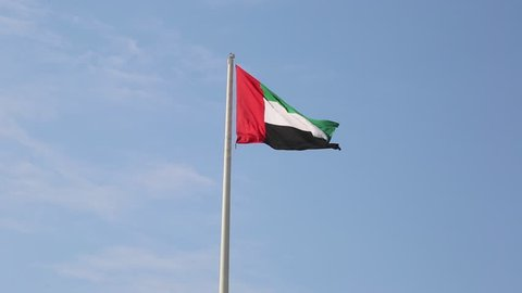 Flag of United Arab Emirates against blue sky in a summer day