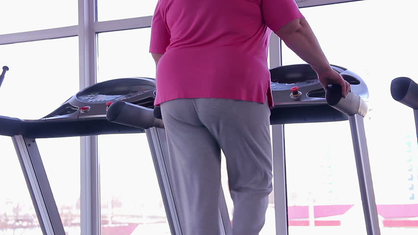 Woman with fat bottom walking on treadmill, active weight loss workout in gym