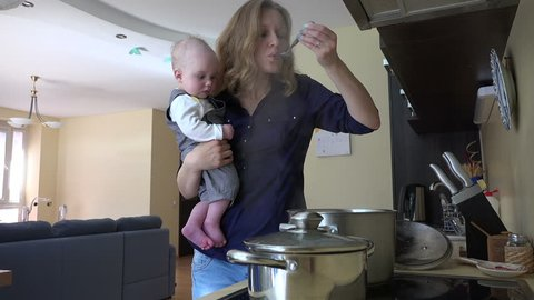 Nanny with infant baby in hands cooking mix meal dish in pot and taste it with spoon. Housewife multitasking at home. Vapor steam rise. Static shot. video clip.