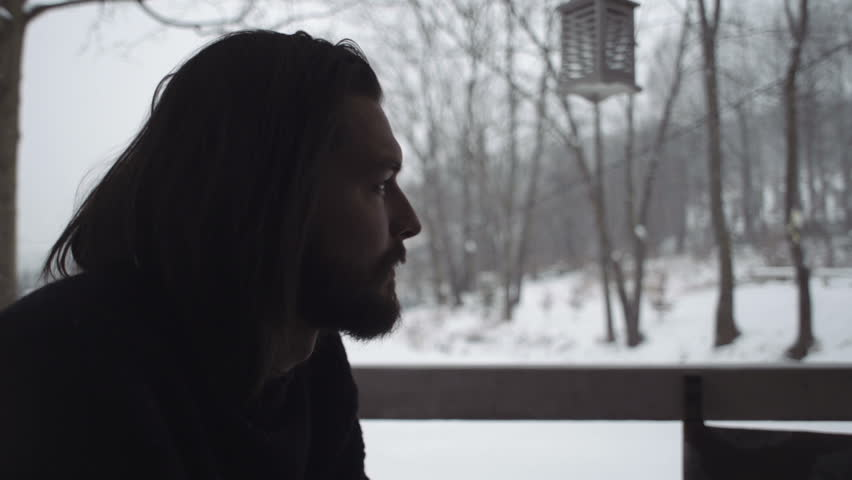 Close up of handsome young man in black sweater sitting by a table on an old wooden porch. Winter scene of thoughtful man sitting by old wooden house. Snowy background. Slow motion.