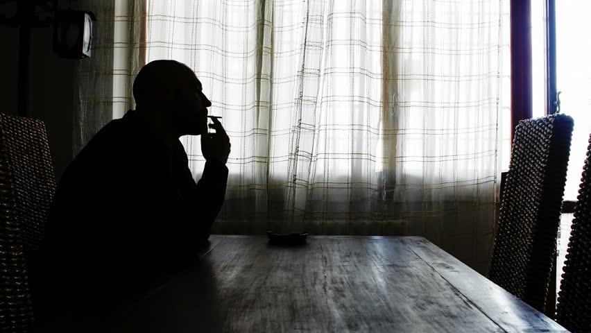 Bald man sat a table smoking a cigarette | Shutterstock HD Video #14858263