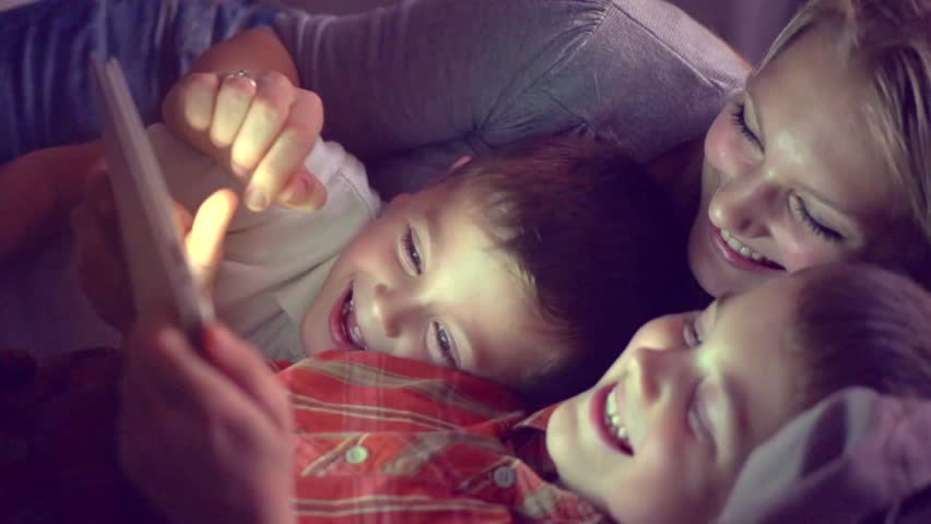 Happy family- mother and Two kids lying down on the sofa and using tablet pc at night. Family watching movie on tablet computer in a dark room, playing games. HD 1080p, slow motion 240 fps | Shutterstock HD Video #14872939