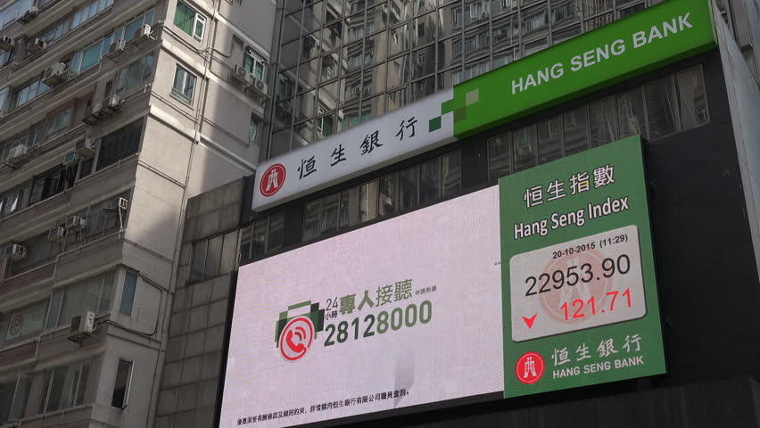 HONG KONG - 20 OCTOBER 2015: Advertising billboard of the Hang Seng Bank displays information about the Hang Seng Stock Exchange index besides a commercial, on the streets of Hong Kong