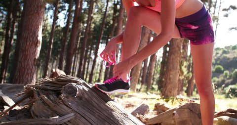 Cropped image of a woman trail runner in colorful sports wear fixing the laces on her modern running shoes before doing some morning exercise
