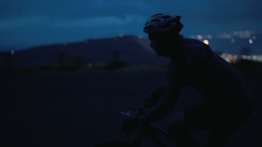 Medium cropped shot of unrecognizable cyclist silhouette riding his bicycle in the dark on a mountain road with the city lights in the background