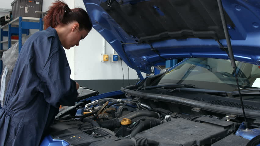 Female mechanic overhauling an engine in the garage