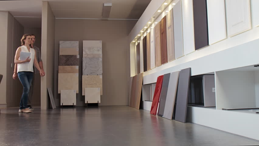Couple Walking Towards Samples In Modern Kitchen Showroom Looking At  Different Finishes Of Cabinets Cupboards
