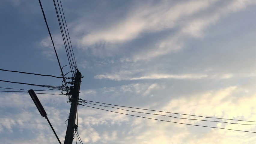 Timelapse clouds with electric pole standing on the foreground, in the evening