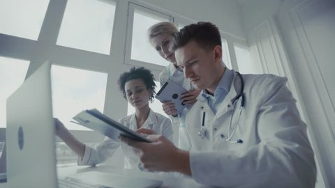 Healthcare, medical: Medical meeting. Group of multi-ethnic doctors discuss and looking x-ray in a clinic or hospital. UHD 4K
