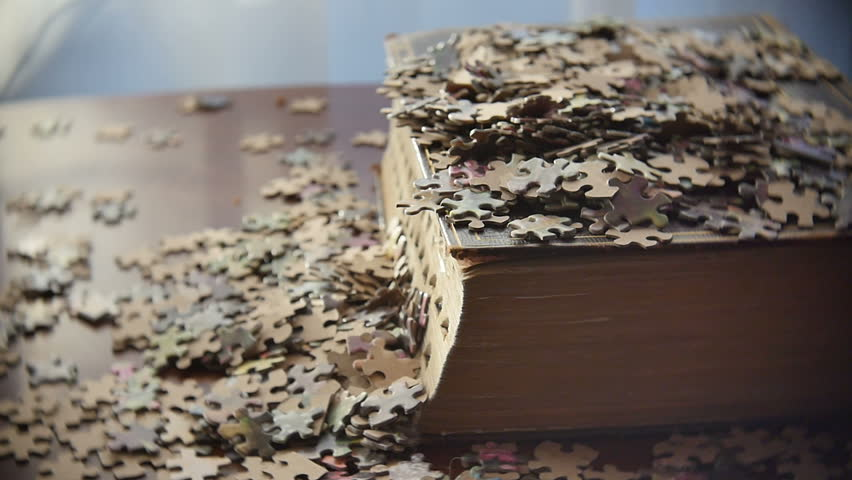 Brushing Puzzle Pieces off Book Representing Knowledge Slow Motion