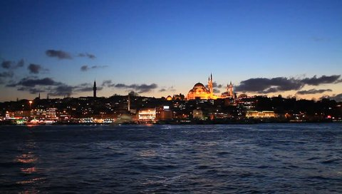 Summer night in Istanbul with reflections from Golden Horn. Suleymaniye Mosque in the distance with lights on