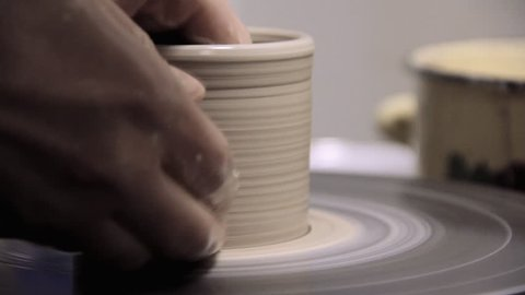 Potter Creates the Product on a Potter's Wheel. on the Potter's Lathe Spinning Pottery. Artist Operate Hands. Hands Gently Create Correctly Shaped Handmade From Clay. God Created Man From Clay. Soft