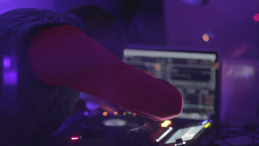 Skilled dj working hard at the mixing console, playing music. People having fun | Shutterstock HD Video #14999893