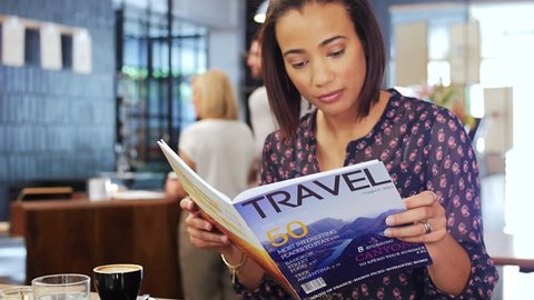 Beautiful mixed race woman reads a travel magazine dreaming of holidays while having coffee in a modern trendy cafe