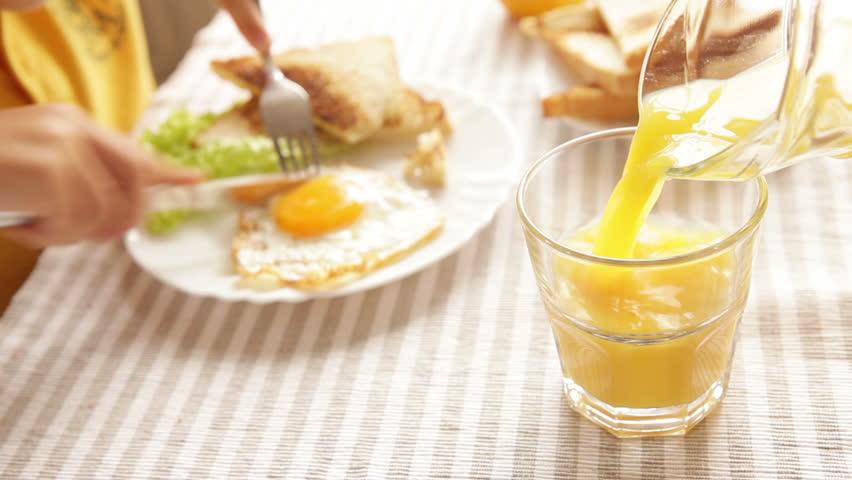 Kid is having his breakfast - fried eggs, toast, juice - before going to school